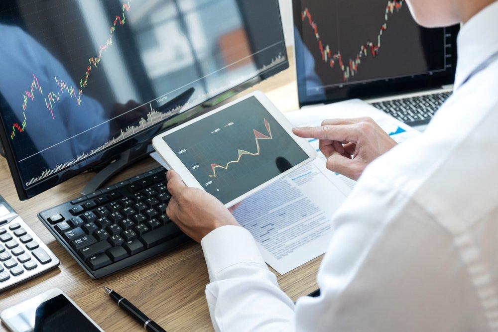 Stock,Exchange,Market,Concept,,Stock,Broker,Looking,At,Graph,Working